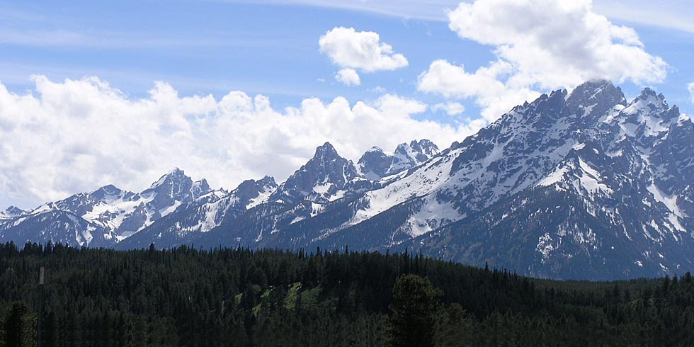 Peaks of the Teton Range form jagged spires. The park's highest peak, the Grand Teton, is veiled by clouds.