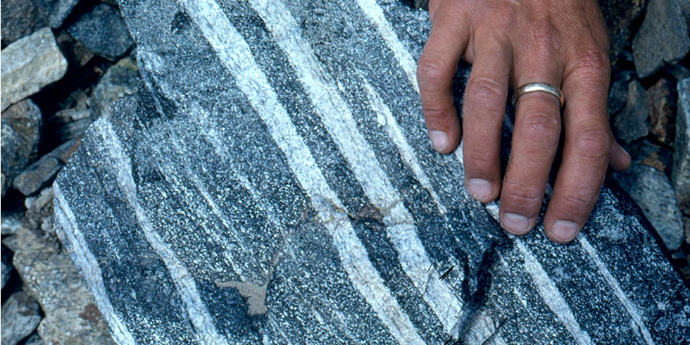 Layered gneiss, with dark gray and white, formed during metamorphism and are not the original rock layers.
